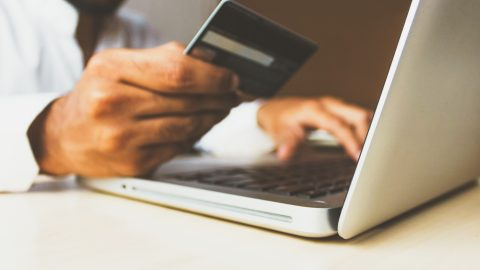 man using computer and holding credit card