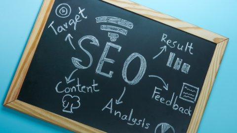 Top view of SEO Search Engine Optimization on black board on blue background