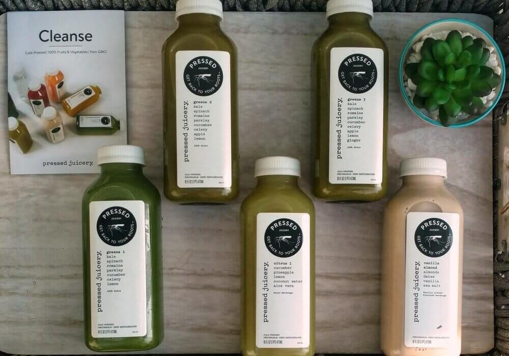pressed juicery bottles with plant and menu